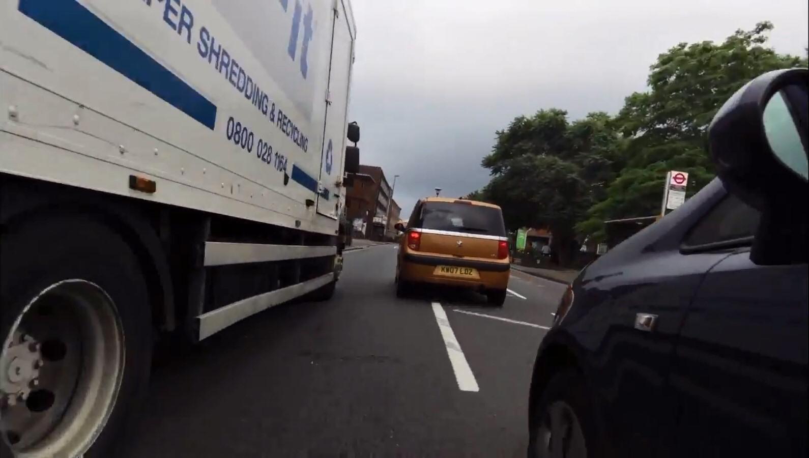 A close pass alongside a parked van.